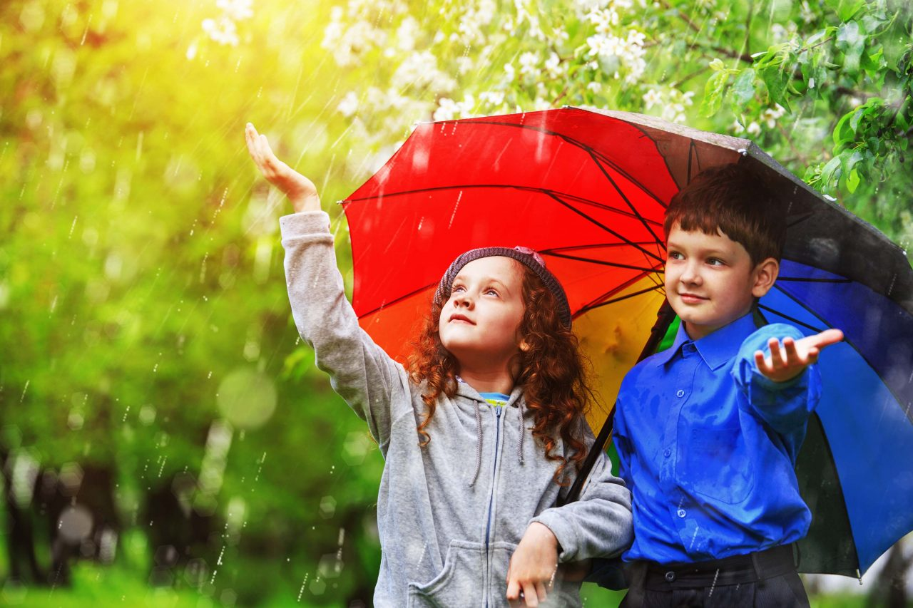Children Under Umbrella Enjoy To Spring Rain Outdoors